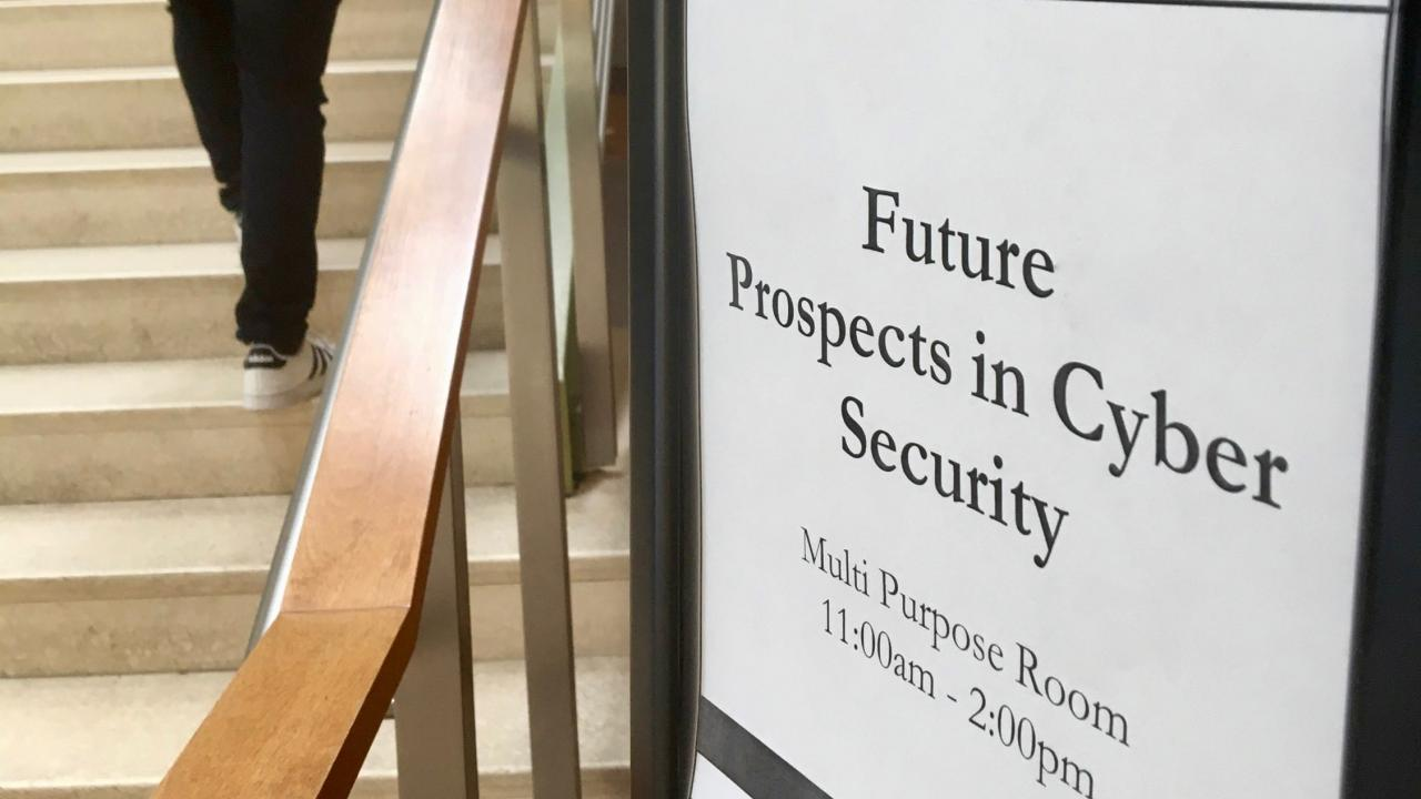 Sign for cybersecurity event, with student on stairs in background